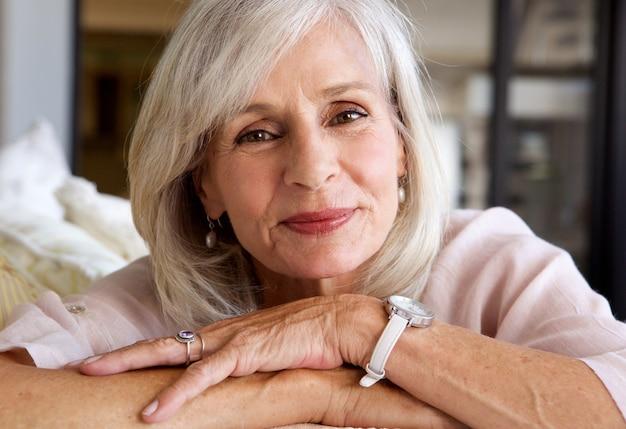 Mulher mais velha descontraída, sorrindo e sentado no sofá