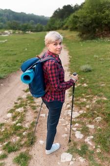 Mulher mais velha do turista com bastões de caminhada