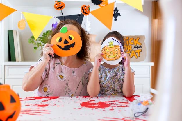 Mulher mais velha e mais jovem, cobrindo o rosto com diferentes tipos de abóboras durante a celebração do halloween.