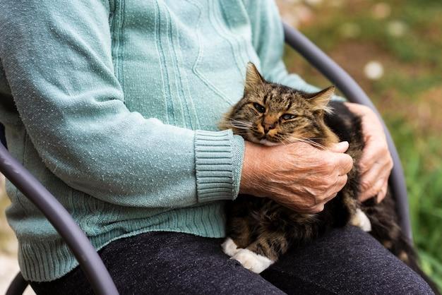 Mulher mais velha em uma casa de repouso segurando um gato