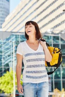 Mulher mais velha feliz carregando mochila por cima do ombro