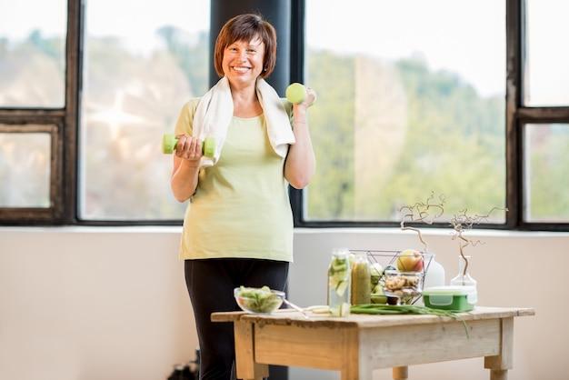 Mulher mais velha feliz em roupas esportivas, treinando com halteres dentro de casa com alimentos saudáveis na mesa