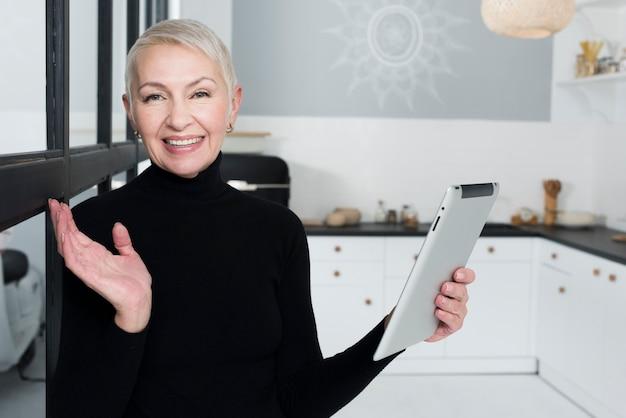 Mulher mais velha feliz na cozinha segurando o tablet