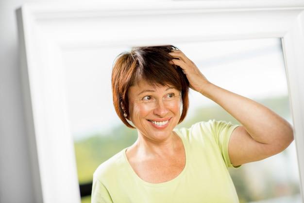 Mulher mais velha feliz olhando para o rosto com um lindo cabelo no espelho