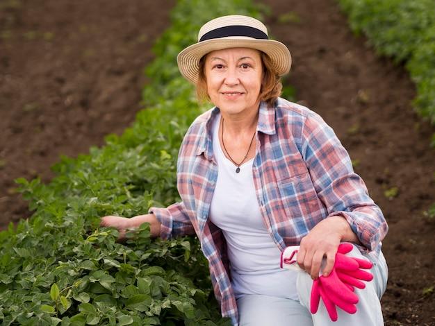 Mulher mais velha, ficar ao lado de uma planta em seu jardim
