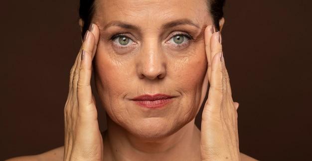 Mulher mais velha maquiada ao posar segurando as têmporas