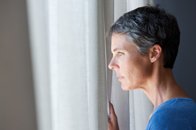 Mulher mais velha, olhando janela