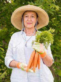 Mulher mais velha, segurando algumas cenouras frescas na mão
