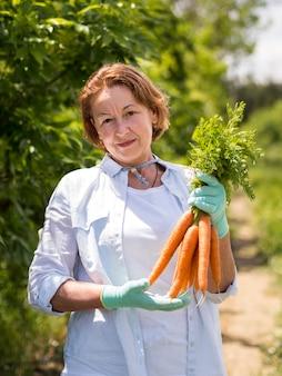 Mulher mais velha, segurando cenouras frescas na mão