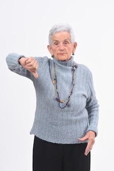 Mulher mais velha, segurando o polegar para baixo e sério no fundo branco