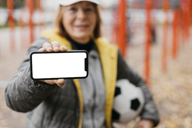Mulher mais velha segurando smartphone e bola de futebol enquanto se exercita ao ar livre