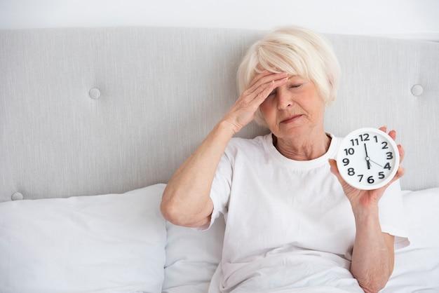 Mulher mais velha, segurando um relógio na cama dela