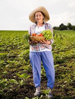 Mulher mais velha, segurando uma cesta cheia de legumes