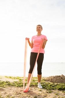 Mulher mais velha sorridente com corda elástica na praia