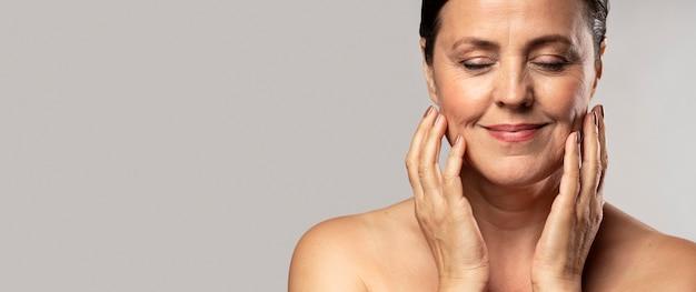 Mulher mais velha sorridente com maquiagem, posando com as mãos no rosto e copie o espaço