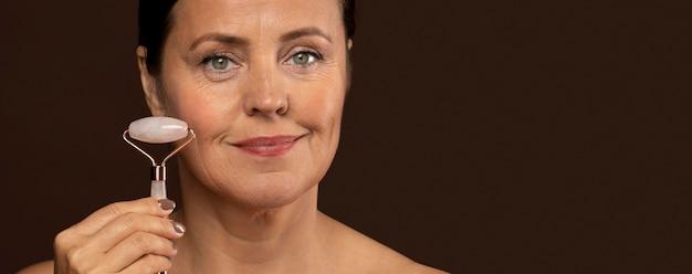 Mulher mais velha sorridente com maquiagem segurando um rolo de quartzo rosa