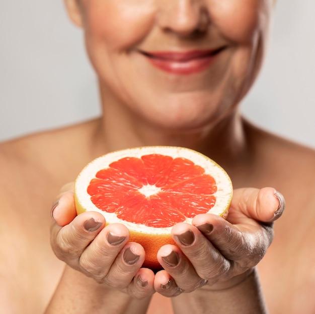 Mulher mais velha sorridente desfocada segurando metade de uma toranja nas mãos