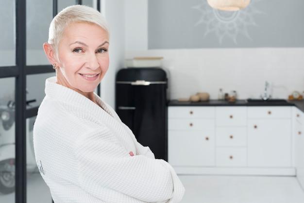 Mulher mais velha sorridente posando em roupão na cozinha