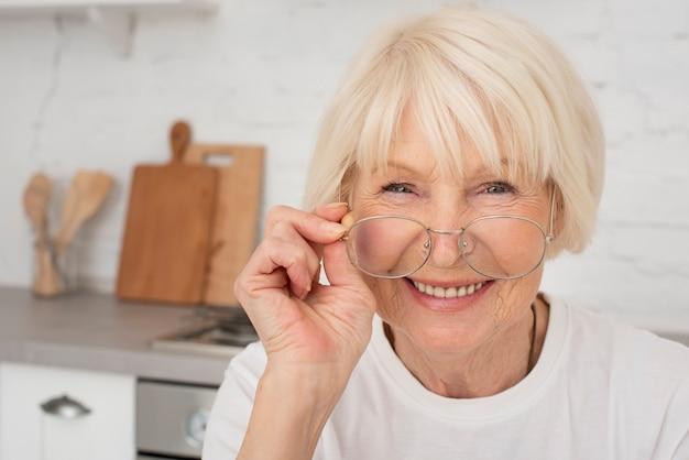 Mulher mais velha sorridente segurando um óculos
