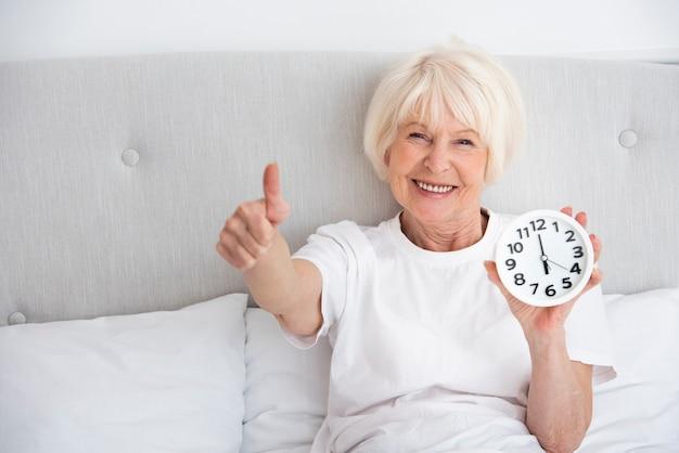 Mulher mais velha sorridente segurando um relógio na cama dela