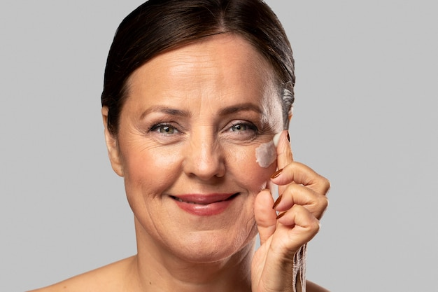Mulher mais velha sorridente usando hidratante no rosto