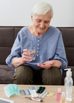 Mulher mais velha tomando seus comprimidos diários
