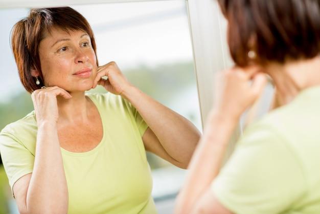 Mulher mais velha triste olhando para o rosto no espelho preocupada com as rugas