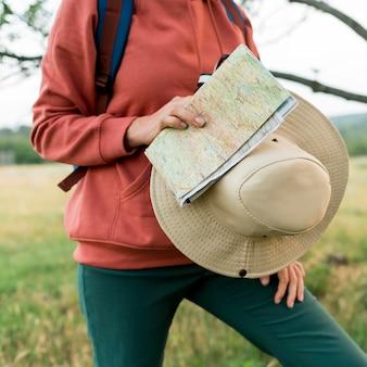 Mulher mais velha turista segurando o chapéu e mapa