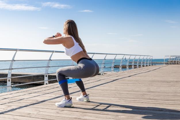 Mulher malhando com borracha fitness.
