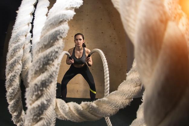Mulher malhando com cordas de batalha