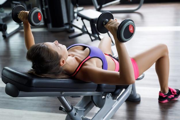 Mulher malhando com halteres no ginásio. supino inclinado. Foto Premium