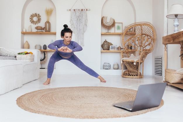 Mulher malhando em casa assistindo a uma aula online.