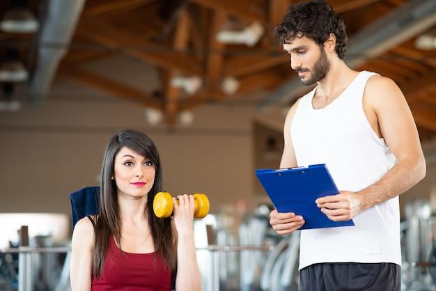 Mulher malhando em uma academia enquanto seu personal trainer observa a execução do exercício