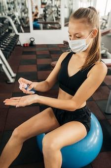 Mulher malhando na academia e usando desinfetante para as mãos