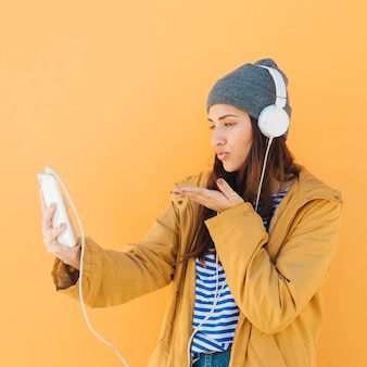 Mulher mandando um beijo online durante uma chamada de vídeo com um telefone inteligente