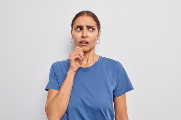 Mulher mantém a mão no queixo parece com uma expressão de descontentamento irritada ao lado usa uma camiseta azul casual em branco