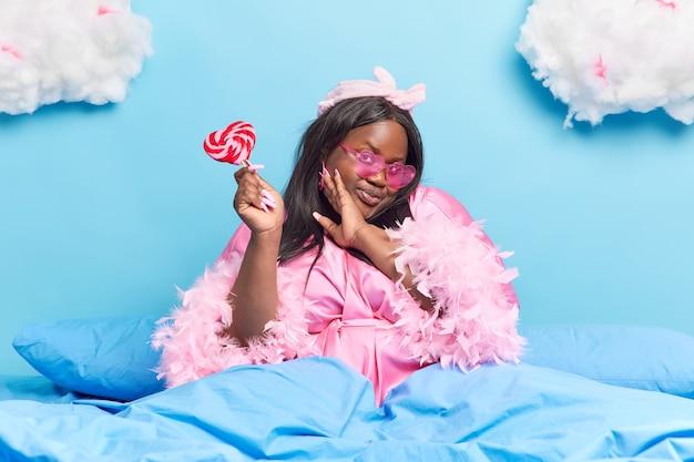 Mulher mantém a mão no rosto aprecia sua pele fresca e escura tem um dente doce segura delicioso pirulito usa roupão senta-se em uma cama confortável isolada no azul