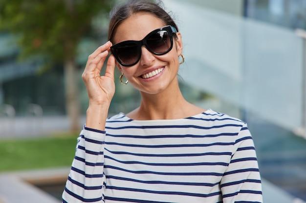 Mulher mantém a mão nos óculos de sol sorrisos agradavelmente vestida com um macacão listrado aproveita o tempo livre no dia de verão tem uma caminhada ao ar livre em poses desfocadas