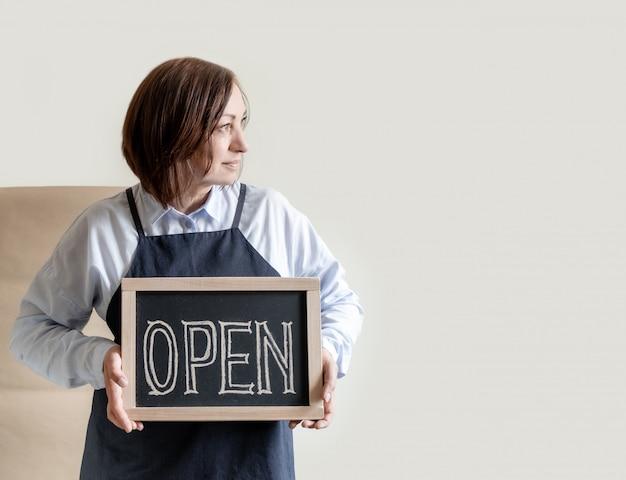 Mulher mantém a placa com o texto aberto. trabalhador no avental mostra a abertura do café ou mercado.