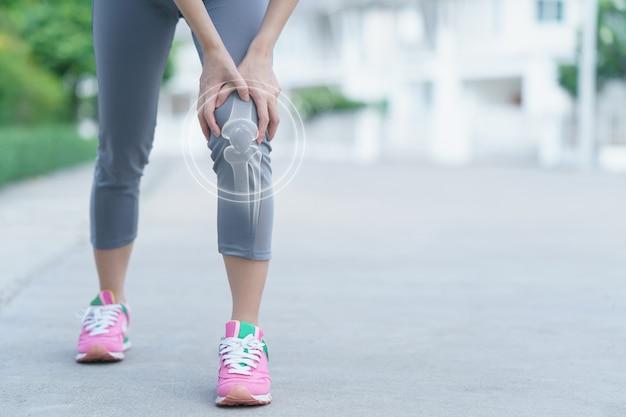 Mulher mantém as mãos no joelho, dor no joelho, medicina, conceito de massagem.