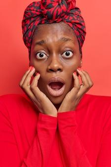 Mulher mantém as mãos no rosto encara os olhos esbugalhados boca aberta parece estupefata usa lenço amarrado na cabeça jumper casual isolado no vermelho