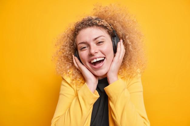 Mulher mantém as mãos nos fones de ouvido sem fio estéreo, sorri, está de bom humor, vestida com jaqueta formal, aproveita o tempo livre