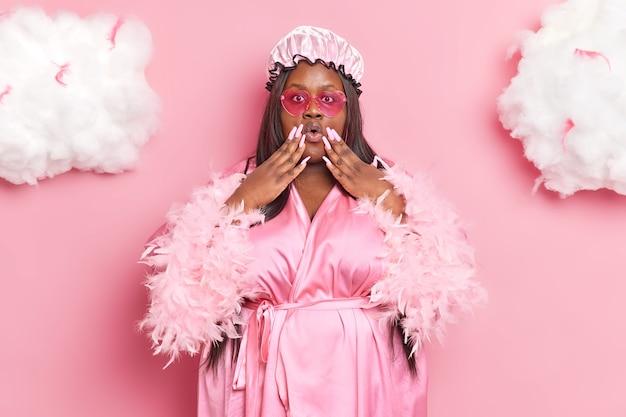 Mulher mantém as mãos perto da boca, usa touca de banho em formato de coração, óculos de sol e roupão tem poses de unhas compridas em rosa
