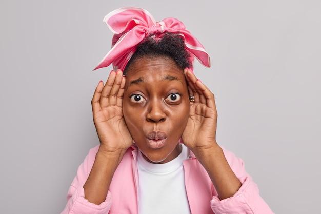 Mulher mantém as mãos perto do rosto olha em descrença parece atônita usa lenço de jaqueta rosa mantém os lábios arredondados isolados no cinza