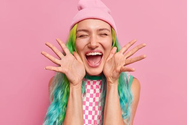 Mulher mantém as palmas das mãos para o lado perto do rosto ri feliz se sente muito feliz mantém os olhos fechados boca bem aberta usa chapéu e vestido isolado em rosa