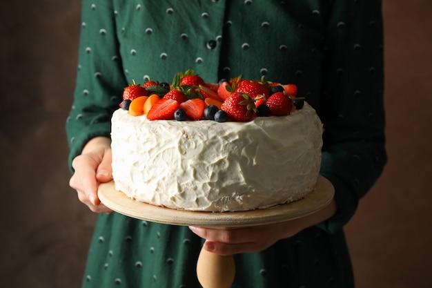 Mulher mantém bolo de creme de baga contra fundo marrom