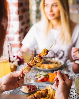 Mulher mantém kebab de frango no espeto de bambu
