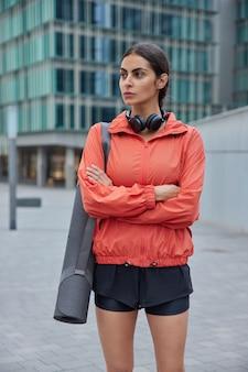 Mulher mantém os braços cruzados olhando para longe fazendo exercícios no tapete de borracha de fitness ao ar livre vestida com roupas esportivas, pronta para o treino
