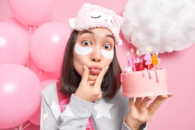 Mulher mantém os lábios dobrados usa máscara de dormir macia e pijama gosta de ambiente doméstico enquanto comemora aniversário com bolo saboroso
