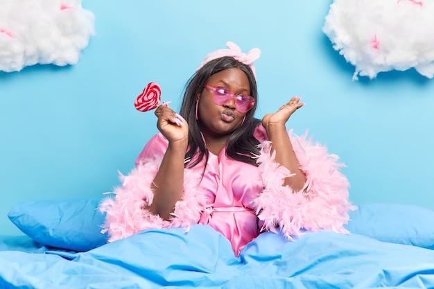 Mulher mantém os lábios dobrados, vestida com elegantes roupas domésticas, usando óculos de sol da moda, segurando deliciosas poses de doces na cama confortável azul